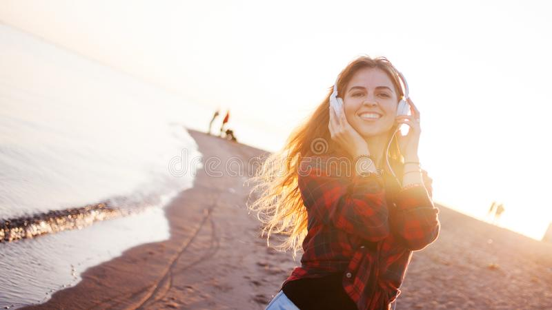 Happy attractive red-haired girl is enjoying favorite music on walk. Beautiful young woman in shirt uses headphones royalty free stock photography