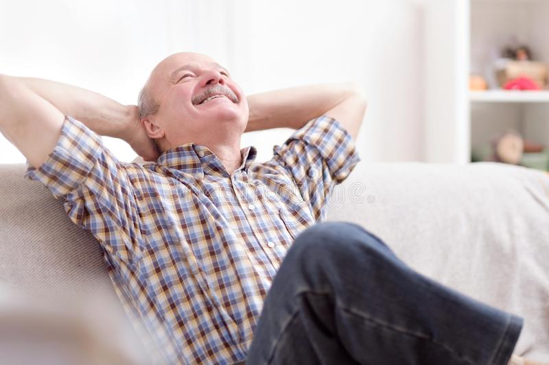 Happy attractive senior man resting and breathing sitting on a couch at home stock photo