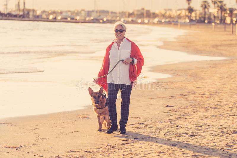 Happy attractive senior woman with her german shepard dog walking on the beach at autumn sunset stock images