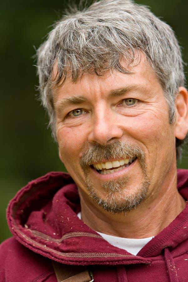 Happy attractive smiling worker. Grey hair hooded sweatshirt royalty free stock image