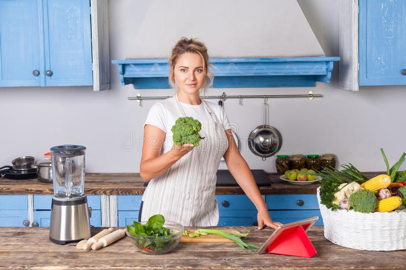 Happy attractive woman in apron holding broccoli and smiling at camera, cooking salad in modern kitchen. Preparing vegetarian food, basket of fresh vegetables stock photo