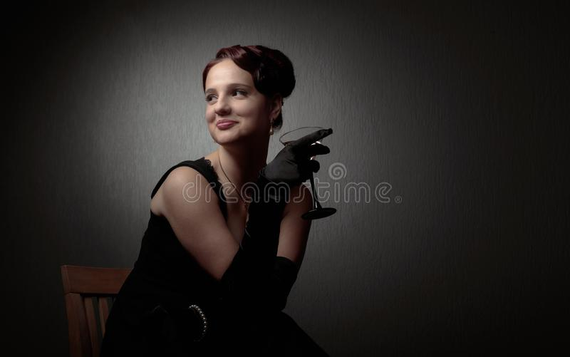 Happy attractive woman in black dress with perfect hair and makeup holding glass of martini. The woman looks away and smiles. Copy space stock photo