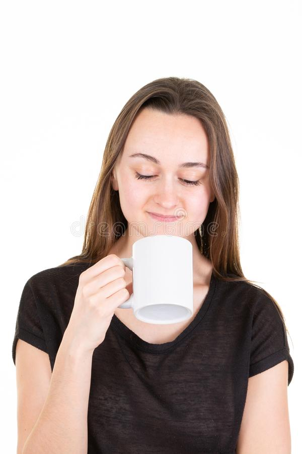 Happy attractive woman with eyes closed drinking cup of tea stock photo