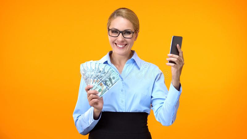 Happy attractive woman formal suit holding smartphone and dollars, banking royalty free stock images
