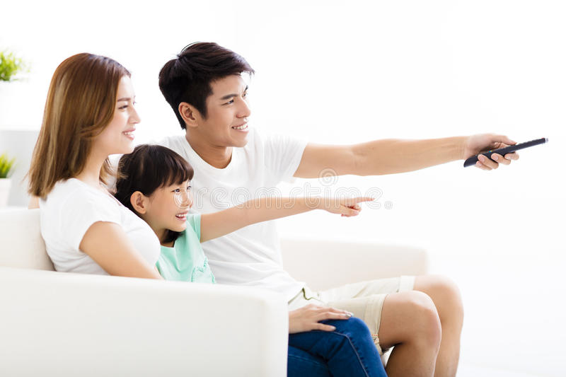 Happy Attractive Young Family watching the tv royalty free stock images