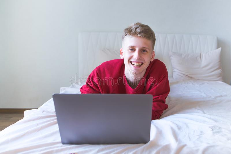 Happy, attractive young man lying home on a bed with a laptop, working, looking at the camera and smiling royalty free stock photography