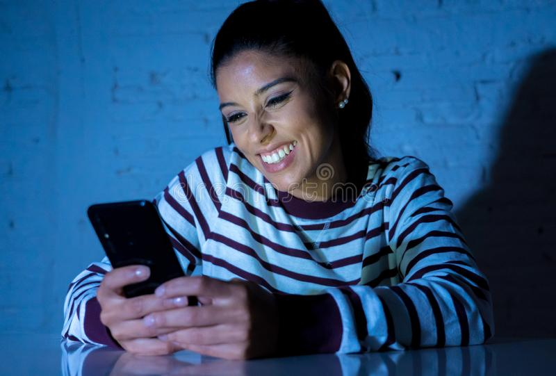 Young beautiful woman flirting and chatting on her smart phone late at night royalty free stock photography
