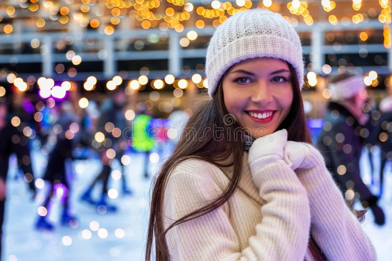 Woman on a Christmas ice rink enjoys the winter feeling royalty free stock image