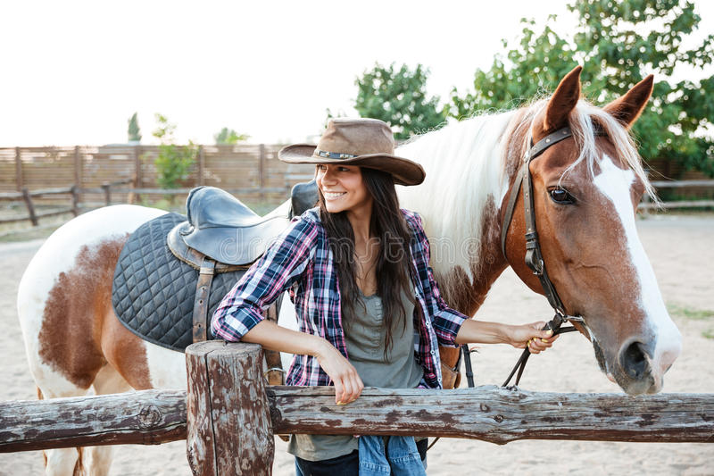 Happy attractive young woman cowgirl with horse on ranch stock photography