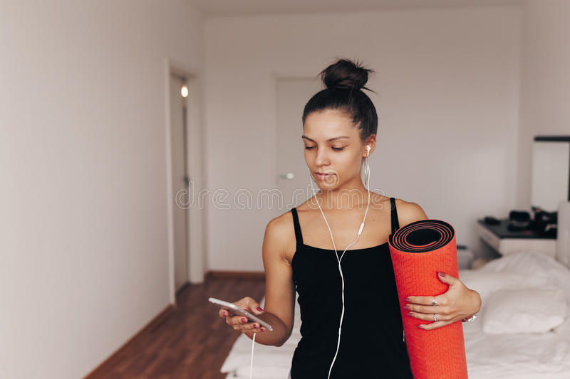 Happy attractive young woman holds in hands red yoga or fitness mat after working out at home in living room. Healthy royalty free stock photos