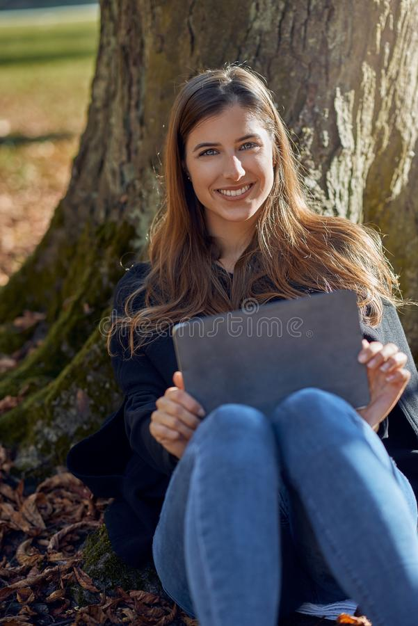 Happy attractive young woman seated under a tree leaning on the trunk royalty free stock image