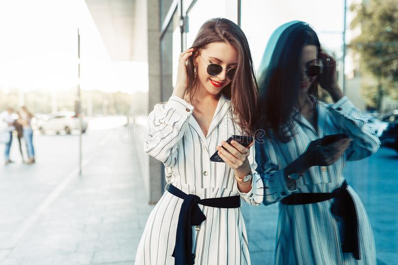 Happy attractive young woman in sunglasses looking at smartphone screen while walking in the city. Dressed in stylish clothes stock image
