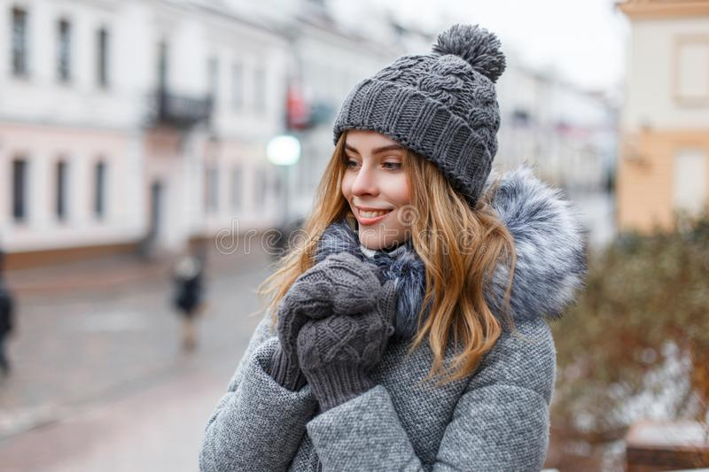 Happy attractive young woman in a winter knitted hat in a trendy gray coat with fur in knitted warm mittens with a beautiful smile. Walks around the city on a royalty free stock images