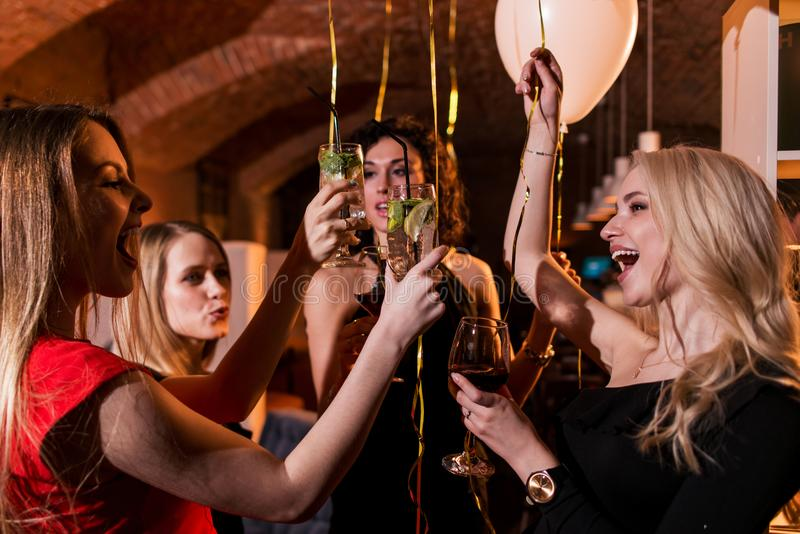 Happy attractive young women having birthday party laughing, dancing, singing, enjoying the night in stylish restaurant.  royalty free stock photography