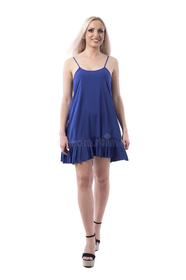 Happy aufgeregte blonde Fashion Catwalk Girl in blauem Kleid laufen und lächeln stockfotos