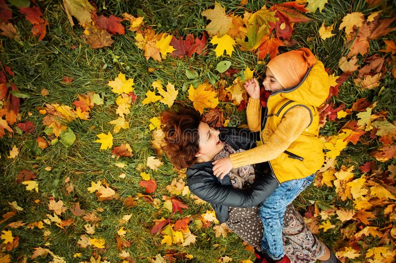 Happy Autumn Family in Fall Park Outdoor. Cheerful Mother and Child Boy having Fun Outdoors stock images
