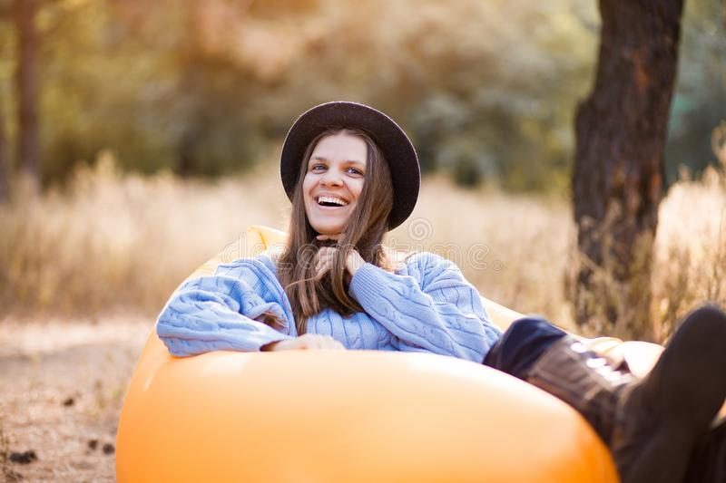Happy autumn portrait of young woman in blue sweater and black hat lying on orange inflatable sofa outdoor in forest stock photos