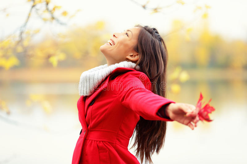 Happy autumn woman blissful. And playful smiling with arms out holding red fall leave by lake royalty free stock photos