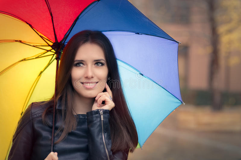 Happy Autumn Woman Holding Rainbow Umbrella out in the Rain. Smiling fall girl wearing leather jacket outside in rainy weather royalty free stock photos