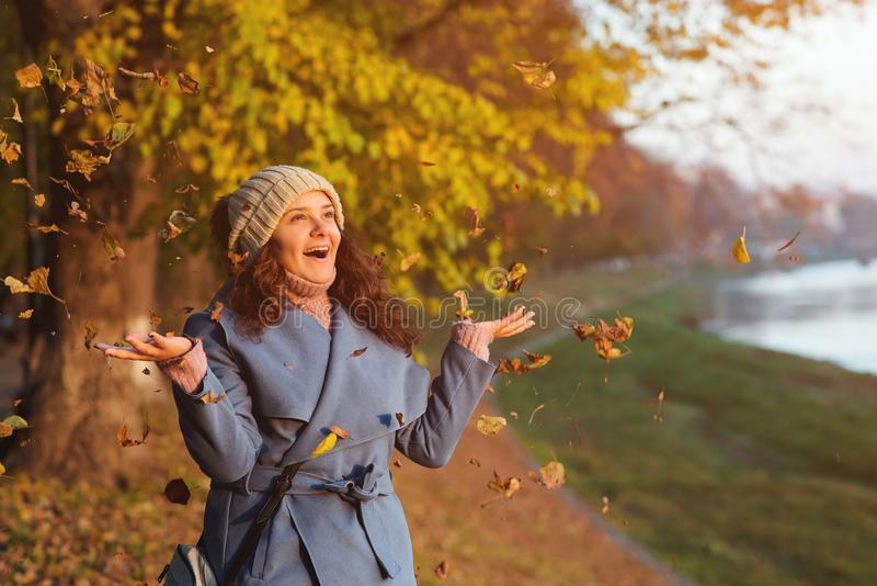 Happy autumn woman portrait. Young woman throws autumn leaves at park. Beautiful girl in blue coat enjoys autumn weather. Woman stock photo