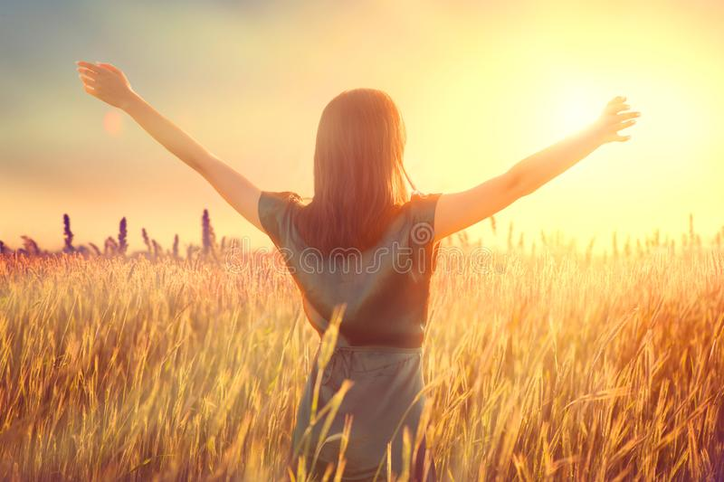 Happy autumn woman raising hands over sunset sky, enjoying life and nature. Beauty female on field looking on sun. Silhouette of girl in sunlight rays. Fresh royalty free stock photography