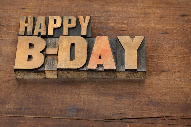 Happy b-day (birthday). Text in vintage letterpress wood type on a grunge wooden background stock images