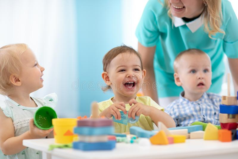 Happy babies in day care. Group of kids playing toys with kindergarten teacher. Children lesson in creche stock image