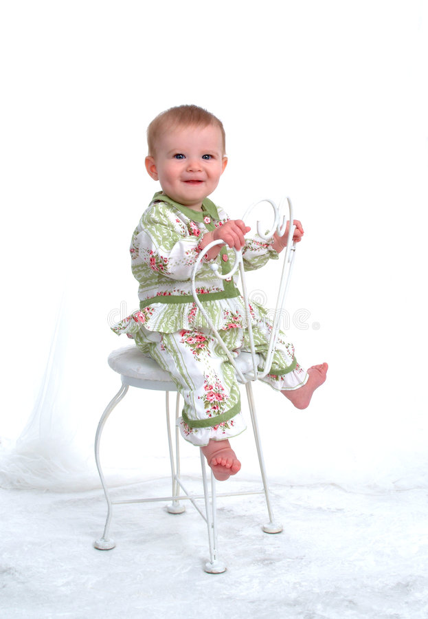 Happy Baby. Girl sitting on a chair backwards holding back of chair royalty free stock photos