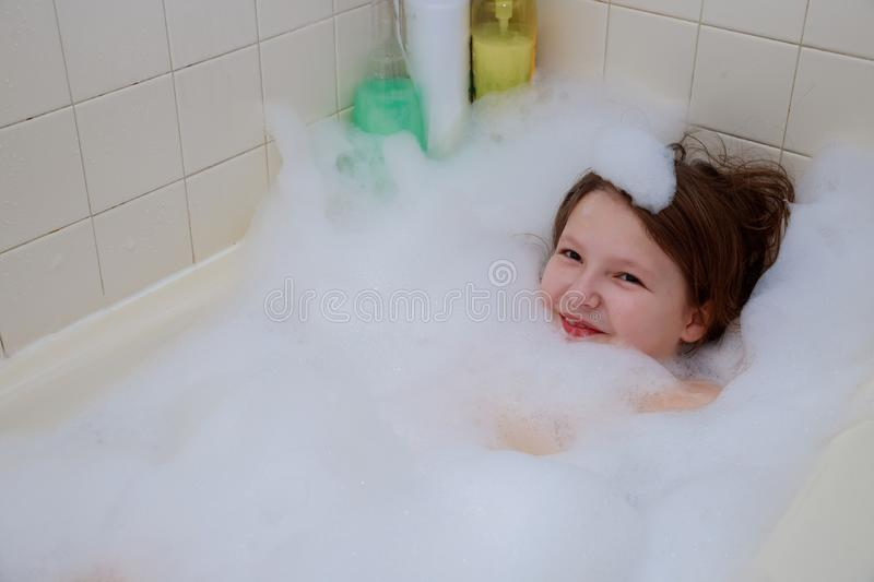 Happy baby in the bath, swimming in the foam shower. Happy baby in the bath, swimming in the foam. Baby shower stock photo