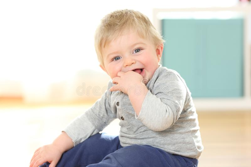 Baby biting fingers looking at camera on the floor. Happy baby biting fingers looking at camera on the floor stock images