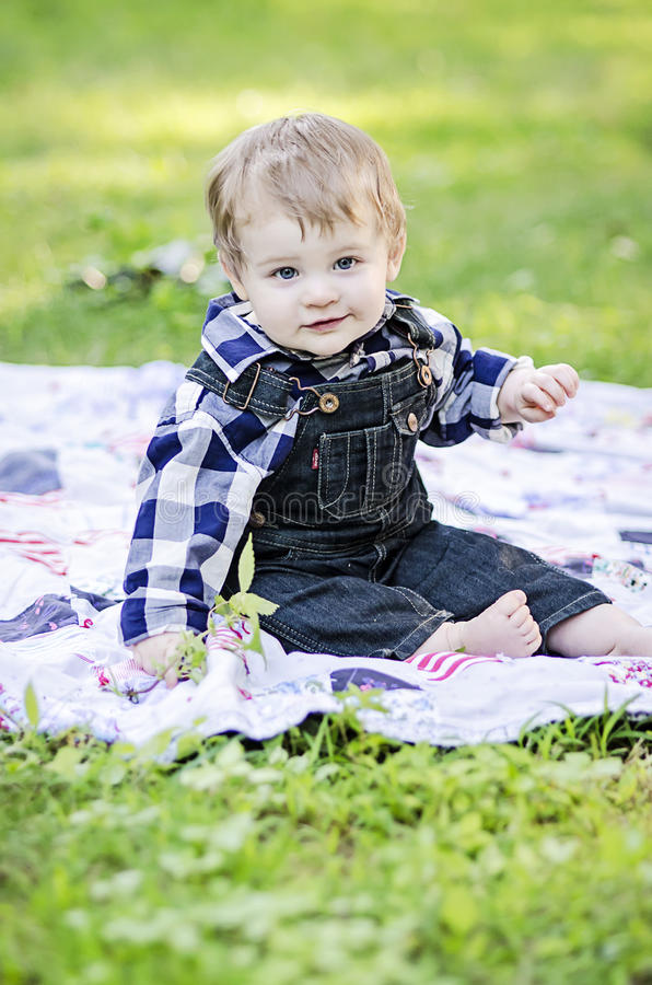 Happy baby. Smiling baby boy on blanket in grass stock photos