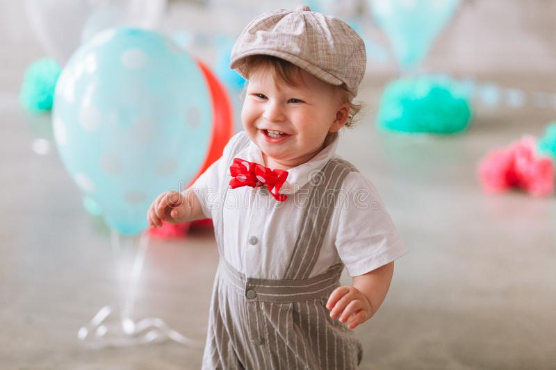Happy baby boy celebrating first birthday. Kids birthday party decorated with balloons and colorful banner royalty free stock images