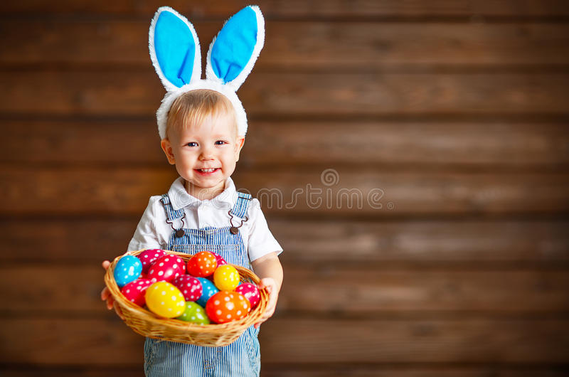 Happy baby boy in Easter bunny suit with basket of eggs stock images