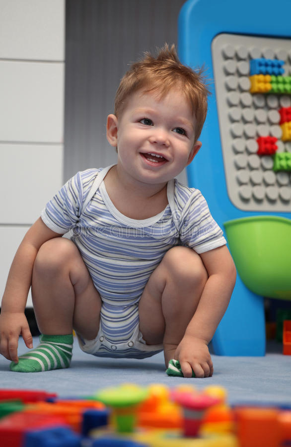 A happy baby boy on a floor royalty free stock photo