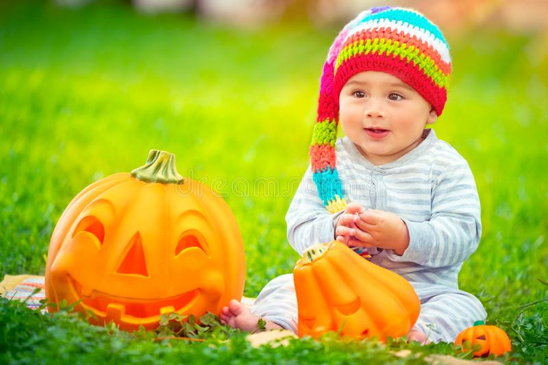 Happy baby boy on Halloween. Holiday outdoors, sitting on green grass backyard, wearing funny festive colorful hat, playing with cute carved pumpkins stock image