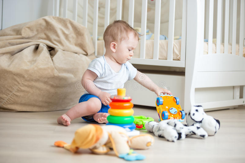Happy baby boy playing with toys on floor at bedroom. Happy little baby boy playing with toys on floor at bedroom stock images
