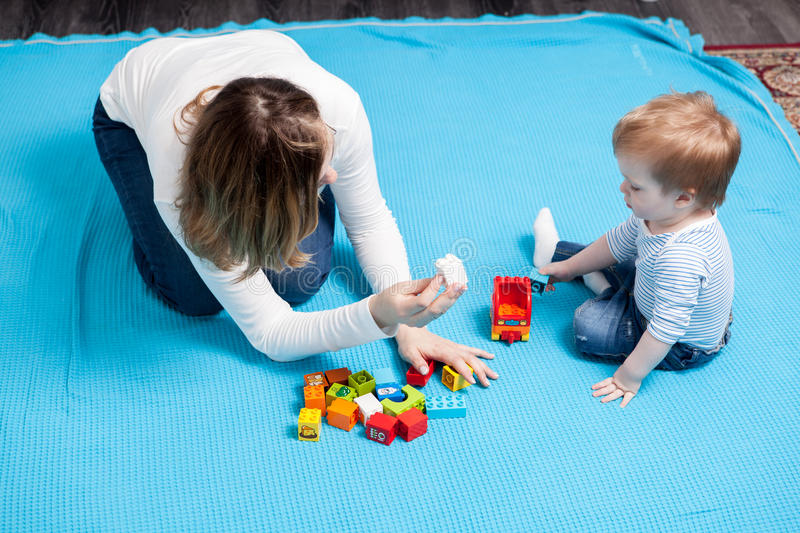 Happy baby boy playing with toys next to her mother stock photo