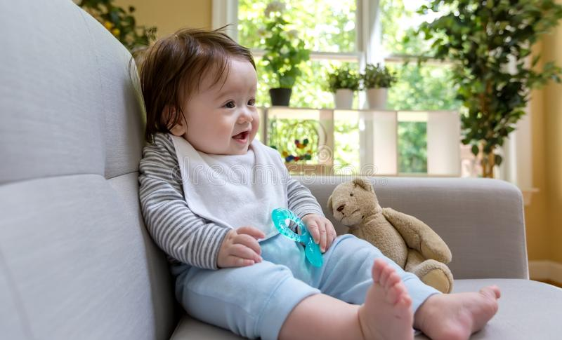 Happy baby boy sitting on a couch royalty free stock photo