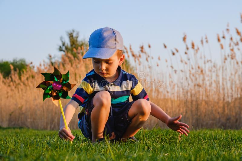Happy baby boy sitting in grass on the fieald at sunny summer evening. Child outdoors with wind wheel on the river bank royalty free stock images