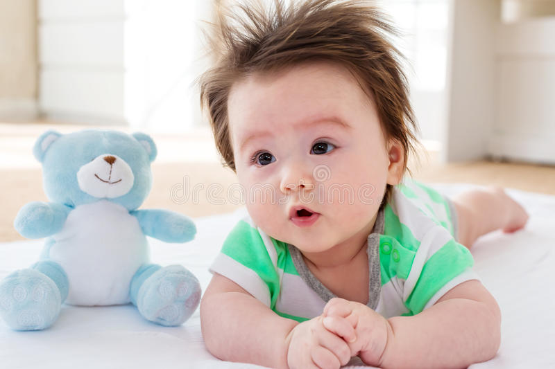 Happy baby boy with teddy bear royalty free stock photography