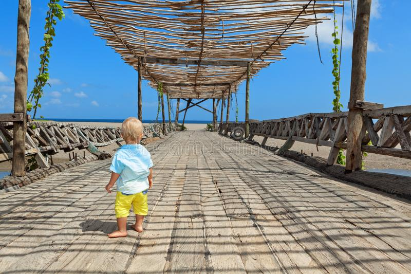 Happy baby boy walk by wood bridge to ocean beach stock photo