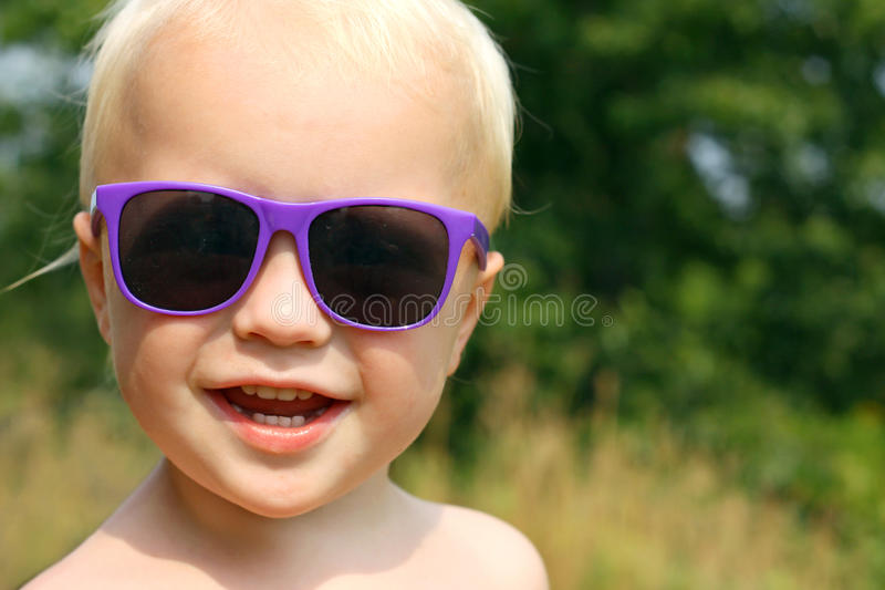 Happy Baby Boy Wearing Sunglasses. Close up portrait of a cute, happy baby boy is wearing purple sunglasses and smiling as he looks at the camera outside on a stock photography