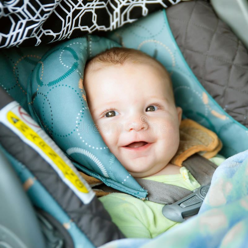 Happy baby buckled into car seat stock photography