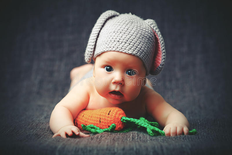 Happy baby child in costume a rabbit bunny with carrot on a grey. Background stock photography