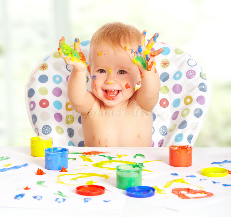 Happy baby child draws with colored paints royalty free stock photography