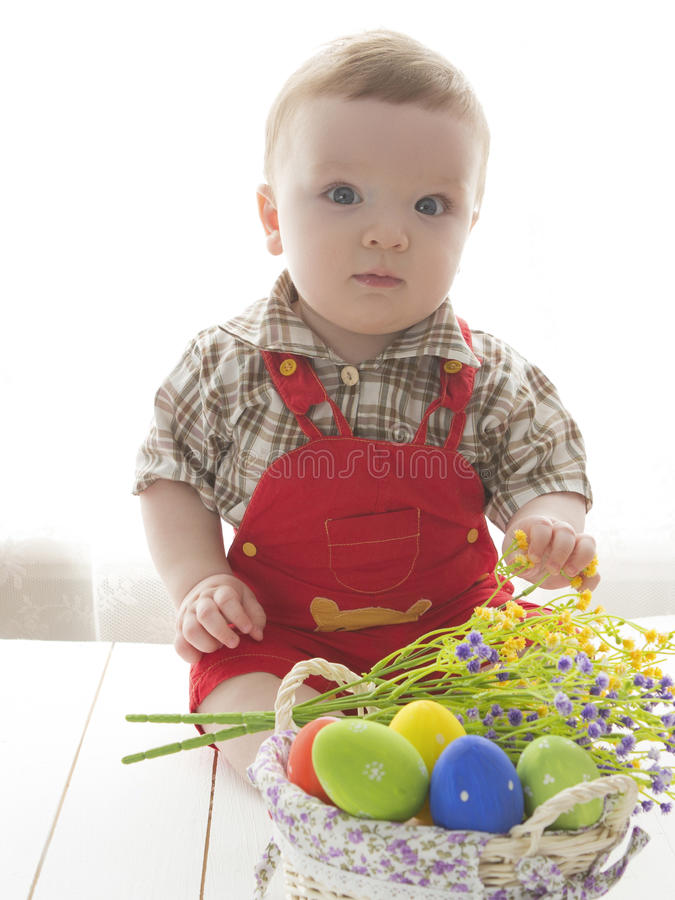Happy baby child with Easter colorful eggs and flowers stock images