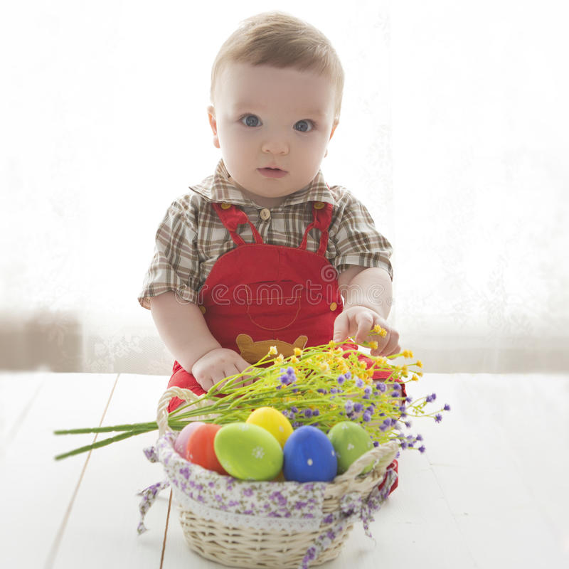 Happy baby child with Easter colorful eggs and flowers stock image