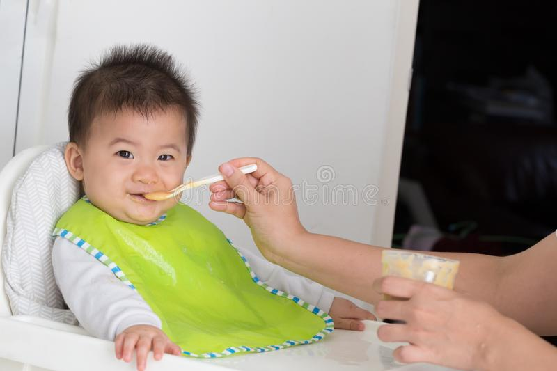 Happy baby child sitting in chair and mother feeding baby boy with spoon in the room at home, stock photo