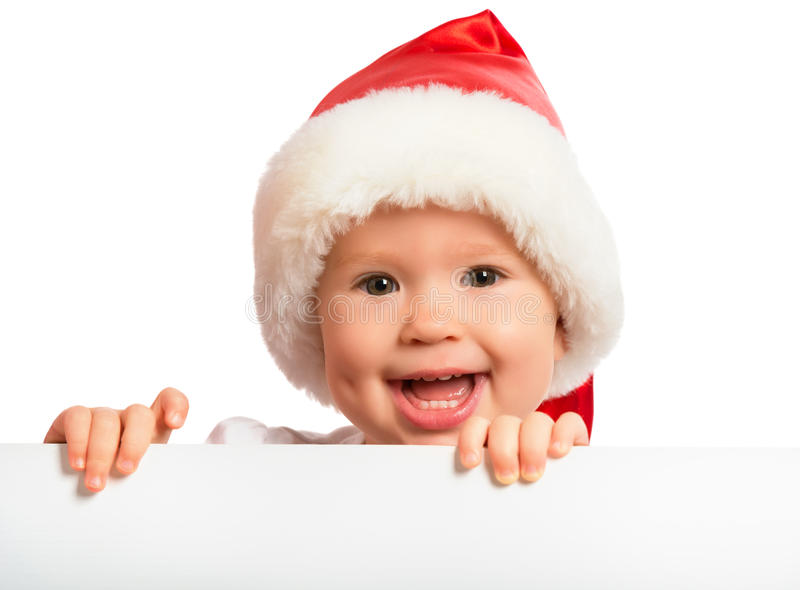 Happy baby in a Christmas hat and a blank billboard isolated on stock photography