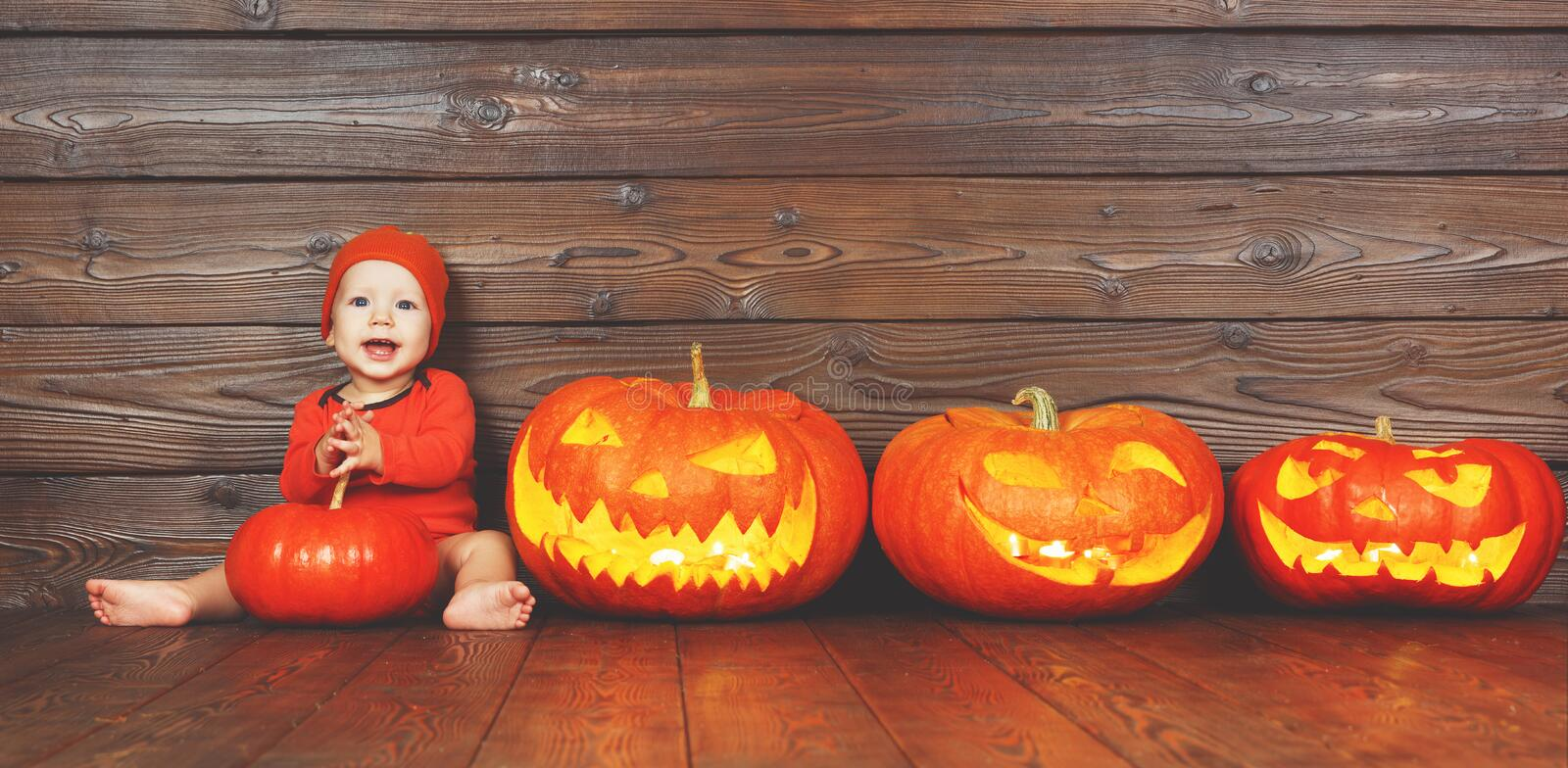 Happy baby in costume for Halloween with pumpkins on wooden back. Happy baby in costume for Halloween with pumpkins with burning eyes on wooden background stock photography